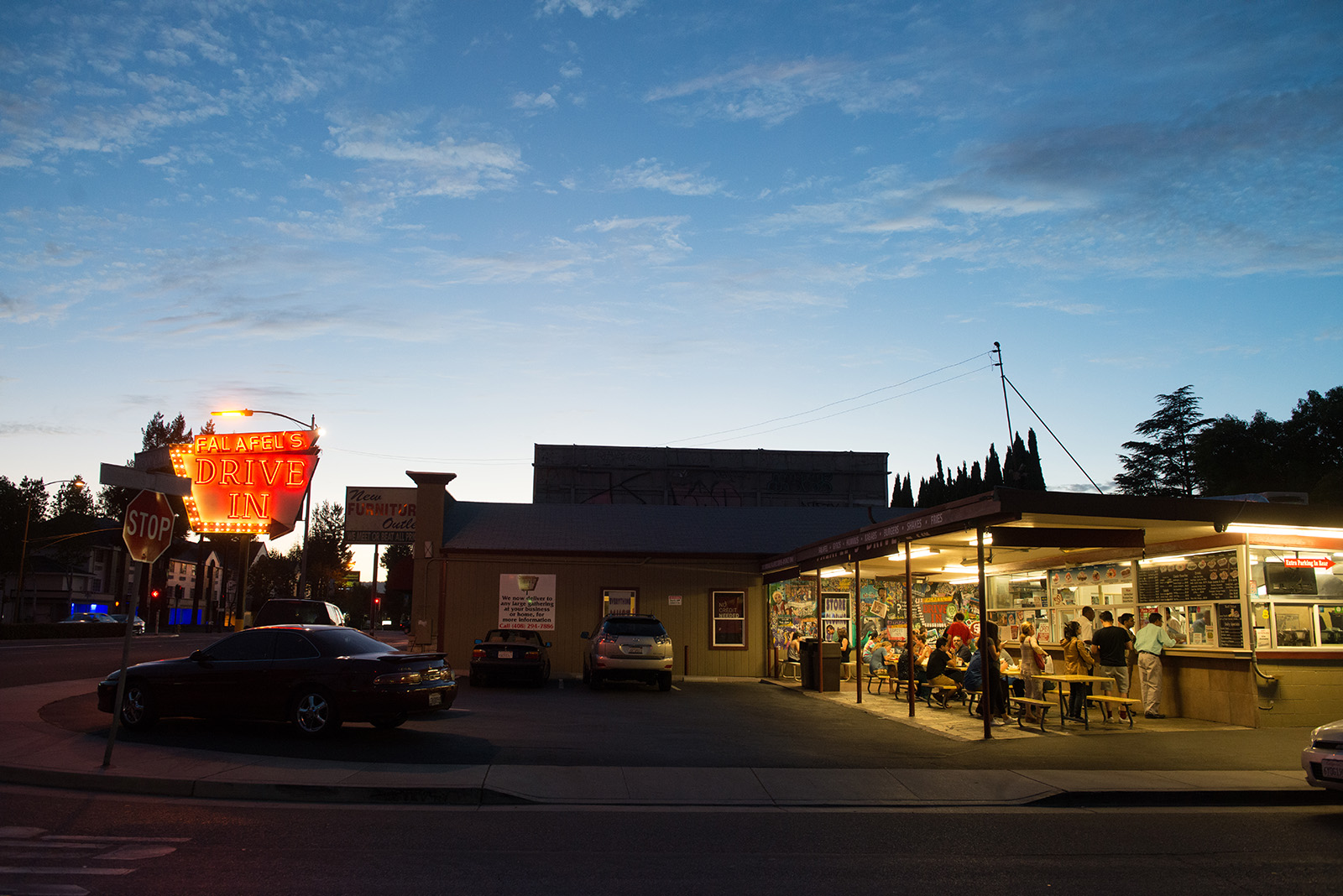 Falafel Drive-In neon sign lit up and people dining outside
